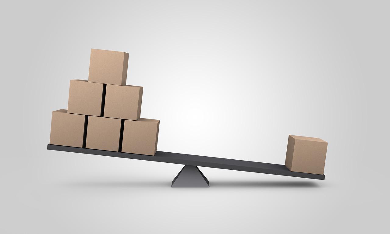 Afbeelding van een weegschaal met dozen, het kleine blok weegt meer dan de grote hoeveelheid blokken