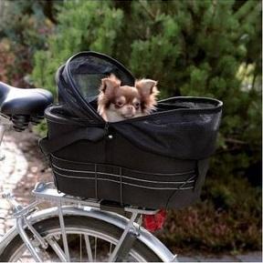 Afbeelding van een hondje achterop in de hondenfietsmand op een elektrische fiets